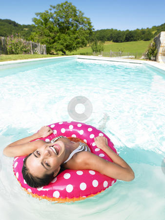 Laughing Woman Floating in Pool stock photo, Woman floating in pink polka dot inner tube and laughing. Vertical. by Mog Ddl