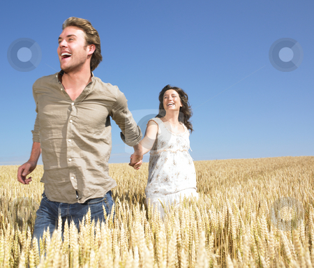 Couple running in wheat field stock photo, Couple holding hands and running in wheat field by Mog Ddl