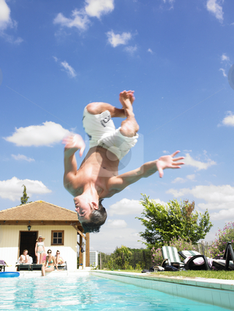 Man Diving Into Swimming Pool stock photo, Man upside down, diving into a swimming pool. Vertical. by Mog Ddl