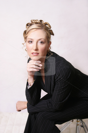 Glamorous Woman stock photo, Glamorous woman in a pinstripe suit sitting on a stool.  This photo could be used for fashion, business, beauty