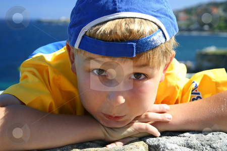 Scallywag stock photo, A boy in a blue cap (backwards) rests his chin on his hands.  He has sunscreen on his face. by Leah-Anne Thompson