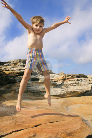 Jump for joy stock photo, Enthusiastic child burns off energy star jumps. by Leah-Anne Thompson