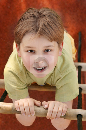 Climbing a rope ladder stock photo, Young boy climbs a rope ladder.Above perspective. by Leah-Anne Thompson