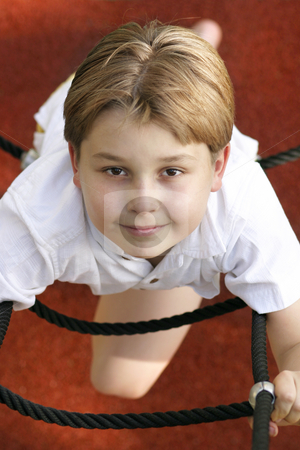 At the playground stock photo, Boy climbs a ladder (above view) . by Leah-Anne Thompson