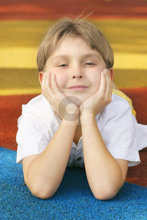 Bright Future stock photo, Boy on colorful playground matting with a happy disposition / outlook. by Leah-Anne Thompson