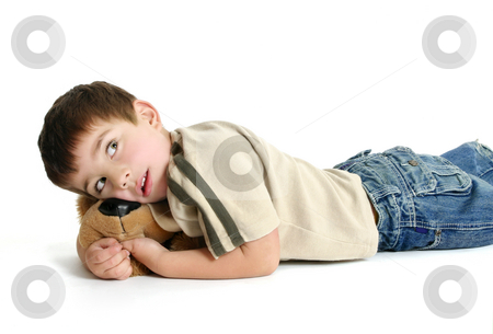 Child resting stock photo, Toddler boy lying on the floor with a toy and thinking. by Leah-Anne Thompson