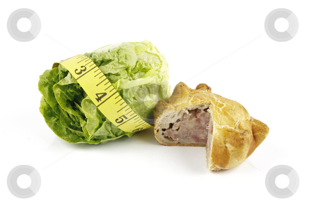 Salad Lettace with Pork Pie and Tape Measure stock photo, Contradiction between healthy food and junk food using a green salad lettace and pork pie with a yellow tape measure on a reflective white background by Keith Wilson