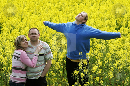 Three people in meadow stock photo, Happy middle-aged couple and their son in flower meadow. by Roberts Ratuts