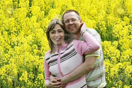 Couple in flower meadow stock photo, Happy and smiling middle-aged couple in the flower meadow. by Roberts Ratuts