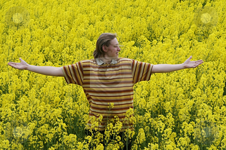 Young man in meadow stock photo, Happy and smiling young man in the yellow flower meadow. by Roberts Ratuts