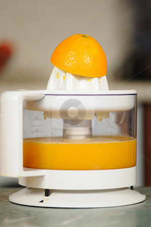 Juice extractor stock photo, Squeezing of orange juice on a juice extractor by Salauyou Yury