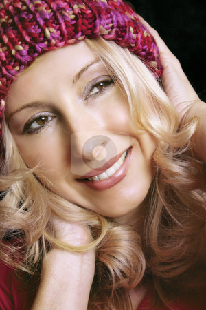 Smile! stock photo, Smiling carefree woman with blonde curling hair and a winter beanie by Leah-Anne Thompson