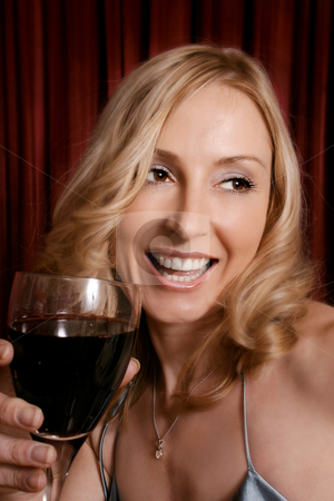 Happy woman drinking red wine stock photo, Happy female holding a glass of red wine by Leah-Anne Thompson