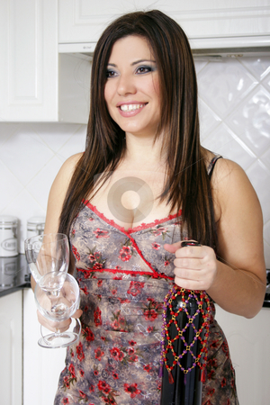 Woman with wine bottle and glasses stock photo, A woman carrying glasses and wine from the kitchen by Leah-Anne Thompson