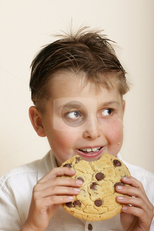 Child eating a very large monster Cookie stock photo, Boy with a very large choc chip cookie. by Leah-Anne Thompson