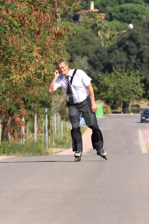 Young businessman stock photo, A young businessman with a roller skate by ARPAD RADOCZY