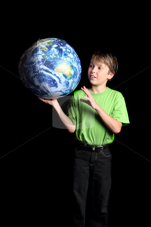Boy holding Earth in his hand and looking with wonder fascinatio stock photo, A young boy student looks at the world with amazement and curiosity against a dark background. Slight motion in left hand by Leah-Anne Thompson