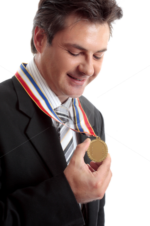 Businessman of the Year stock photo, Business awards.   Businessman admires his gold medal by Leah-Anne Thompson