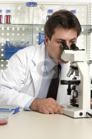 Scientist looking through microscope stock photo, Scientist, biologist, geneticist,  researcher  or healthcare worker studying an object under the microscope by Leah-Anne Thompson