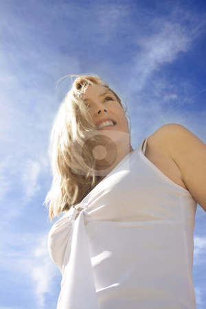 Happy Optimist - smiling female agaisnt a vivid blue sky stock photo, A young woman with windswept hair has an optimistic outlook.  Angled view against pretty windswept clouds. by Leah-Anne Thompson