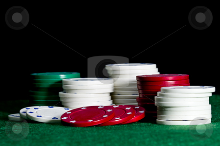 Casino chips on a poker table stock photo, White, red and green poker chips on green felt with a black background by Jodie Johnson