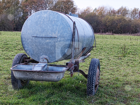 Water container stock photo, Metal water container in a countryside meadow by Laurent Dambies