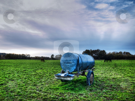 Water container stock photo, Metal water distribution system in a field under dramatic sky and horses on the background by Laurent Dambies