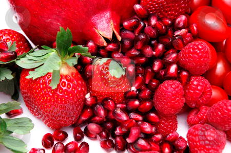Bright Red Fruit stock photo, Different red fruits including a whole Pomegranate and the little ruby seeds, strawberries and raspberries on white by Lynn Bendickson