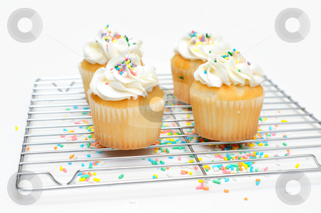 Cupcakes And Wire Cooling Rack stock photo, White cupcake with topping and multi colored sprinkles on top of the cakes and under the baking rack by Lynn Bendickson