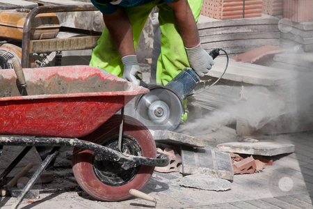 Construction Site stock photo, Worker cutting stone at a construction site. Horizontally framed shot. by Erwin Johann Wodicka
