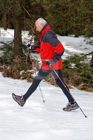 Senior Male Walking in Snow stock photo, Senior male walking in snow with ski poles. Vertically framed shot by Erwin Johann Wodicka