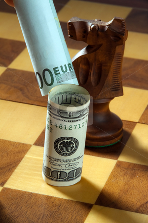 Currency on Chessboard stock photo, Euro tipping over dollar on chessboard. Vertically framed shot. by Erwin Johann Wodicka