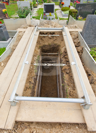 Uncovered Grave stock photo, Empty and open grave in a cemetery. Vertically framed shot. by Erwin Johann Wodicka