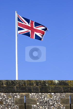 British flag stock photo, British flag flying over a castle battlement in England with a blue sky background by Darren Pattterson