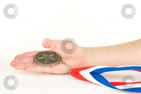 Child's Hand Holding Medal stock photo, Child's hand holding a medal on white background. by Tammy Abrego