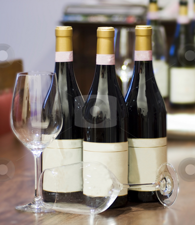 Bottles and glasses stock photo, Three bottles of wine and two glasses over a wooden table by Fabio Alcini