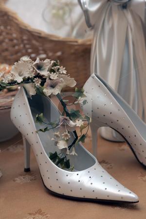 Bridal wedding shoes stock photo, Closeup of luxurious silver bridal wedding shoes indoors. by Martin Crowdy