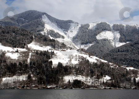 Alpine lake and mountains stock photo, Scenic view of alpine lake and forested mountains in winter, Zell am Zee resort, Austria. by Martin Crowdy
