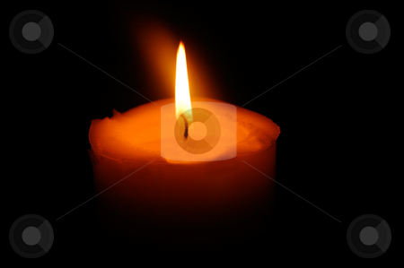 Burning candle stock photo, Closeup of single burning candle isolated on black background. by Martin Crowdy