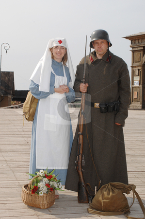 Retro style picture with nurse and soldier stock photo, Old style picture with woman in nurse costume and man in soldier uniform with weapon. Costumes are authentic to the ones weared in time of  World War I. by Roberts Ratuts