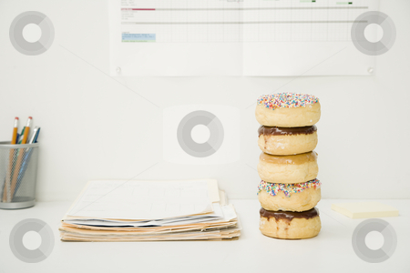 Office Desk With Stack of Donuts stock photo, Office desk with files, a container with pens and pencils, and a stack of five donuts. No one is viewable in the shot. Horizontally framed shot. by Paul Burns