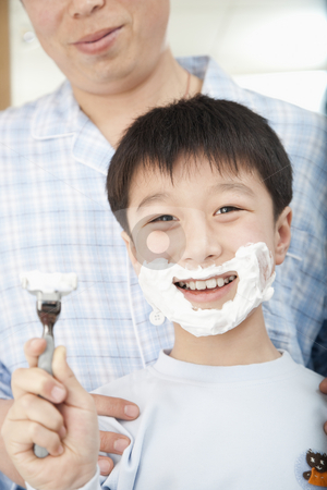 Boy With Shaving Cream on Face stock photo, Father teaching young boy to shave.  Vertically framed shot. by Paul Burns