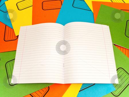 Notebook stock photo, Open lined notebook at the stack multicolored notebooks background by Sergej Razvodovskij