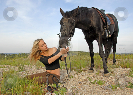 Teenager and black stallion in nature stock photo, Blond teenager and her black horse in a field by Bonzami Emmanuelle