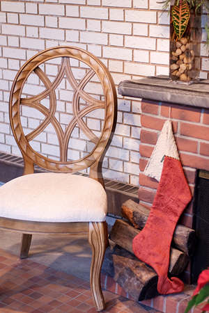 Stocking On Fireplace stock photo, A Christmas stocking hung by the fireplace with a wooden chair beside it by Richard Nelson