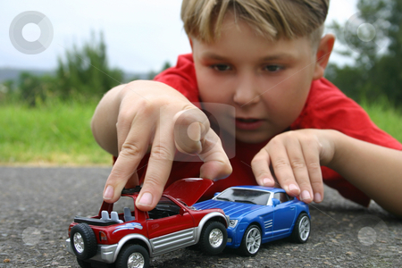 Crash Boy Playing With Toy Cars Outside Stock Photo