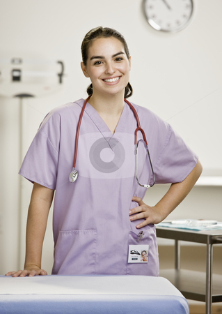Young Female Medical Professional stock photo, Young female medical professional in examination room. Vertically framed shot. by Jonathan Ross