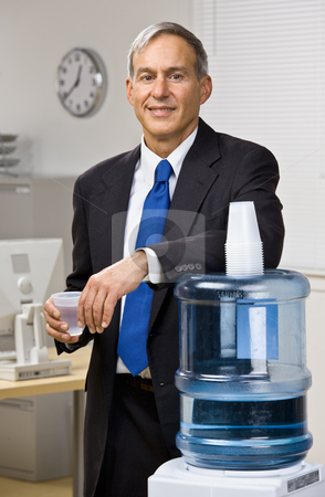 Businessman getting water from water cooler stock photo, Businessman getting water from water cooler by Jonathan Ross