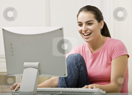 Young Woman Using Computer stock photo, Young woman using desk top computer. Horizontally framed shot. by Jonathan Ross