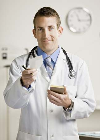 Young Male Doctor stock photo, Young male doctor writing prescription. Vertically framed shot. by Jonathan Ross